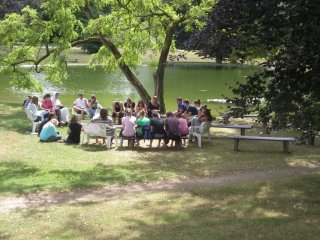 A group of teenagers speaking with a sister at the lake