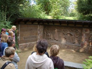 A group of teenagers standing before a relief in the garden of Jesus' suffering