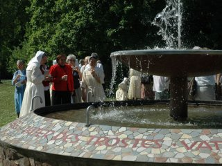 Sisters and guest drinking at the father-fountain